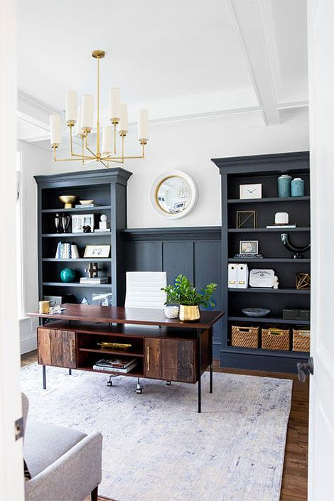 Stylish home office with wooden desk and black shelves