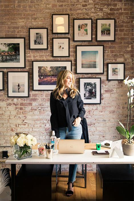 Home office with with framed images and bare brick walls
