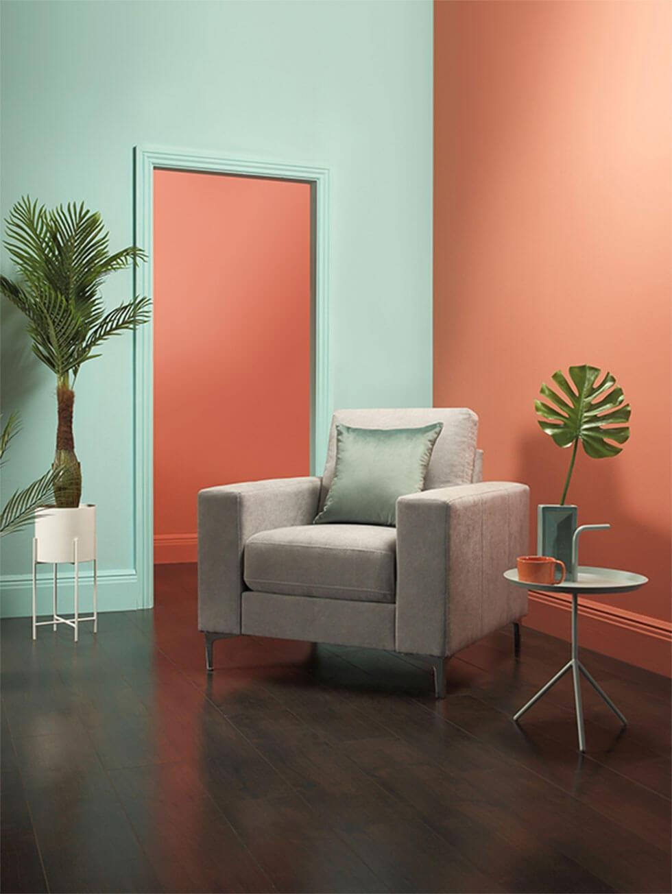 Neo mint and coral colour blocked walls with a light grey armchair