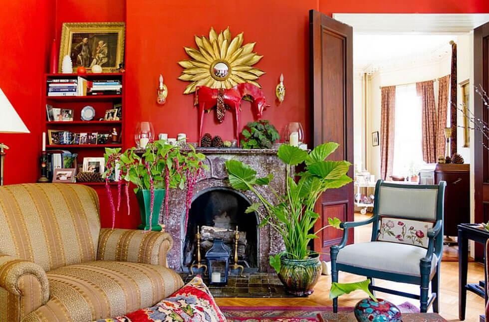 Eclectic red living room with lots of prints, decor and greenery