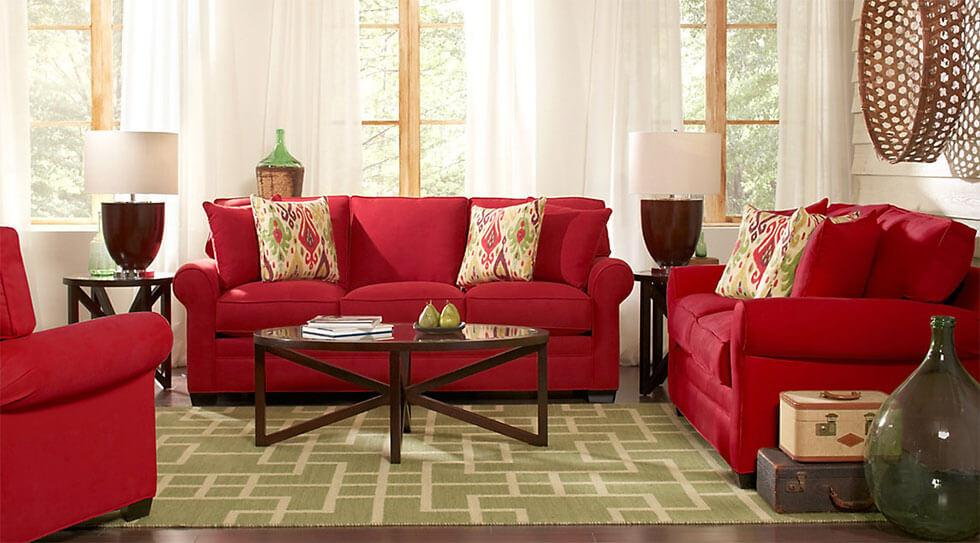 Red sofa suite with green rug and woven basket decor