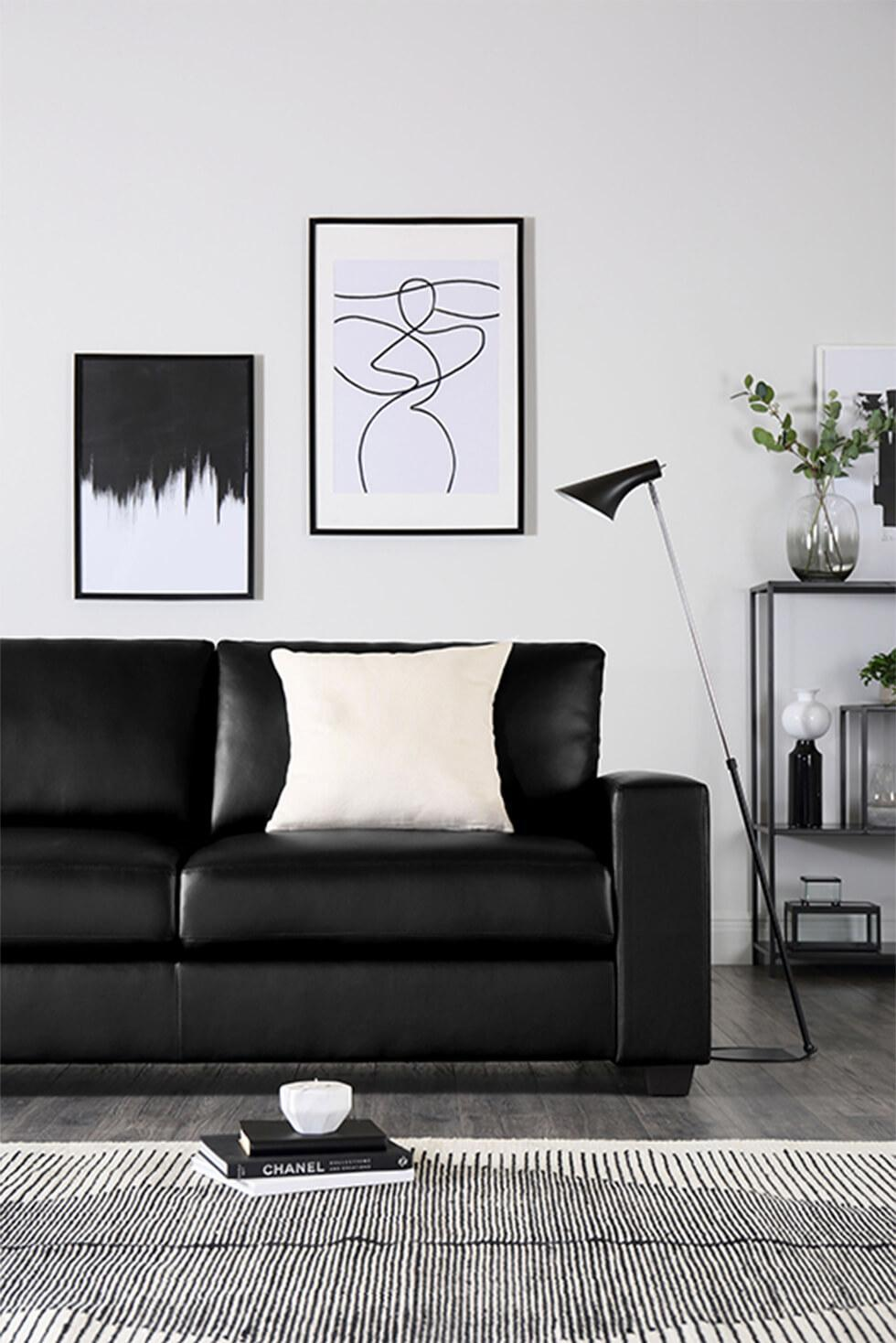 Clean monochrome living room with black leather sofa, framed art, striped rug and white cushion