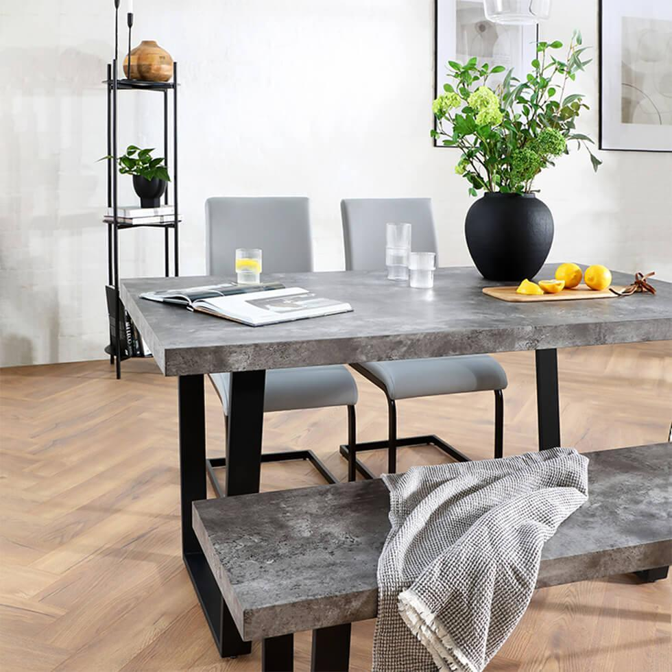 Industrial dining room with concrete dining table and bench and grey leather chairs with a vase of flowers