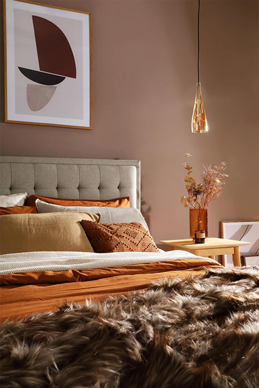 Warm glamorous bedroom with beige fabric bed, orange and brown bedding, fur throw and brass lighting