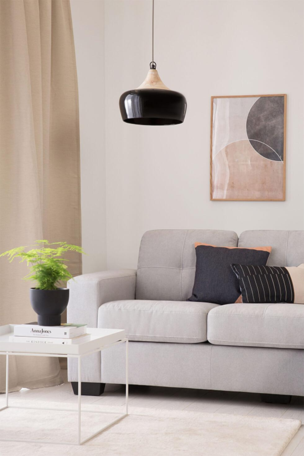 Neutral greige living room with grey sofa, black lamp and white coffee table