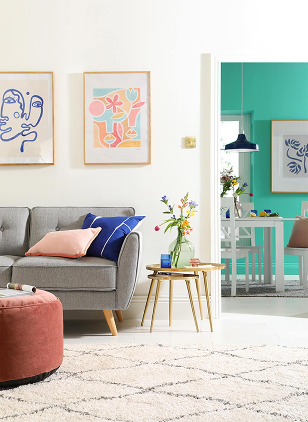Neutral living room with grey sofa, velvet pouffe, pink and blue cushions and flowers, with a view to a turquoise dining room