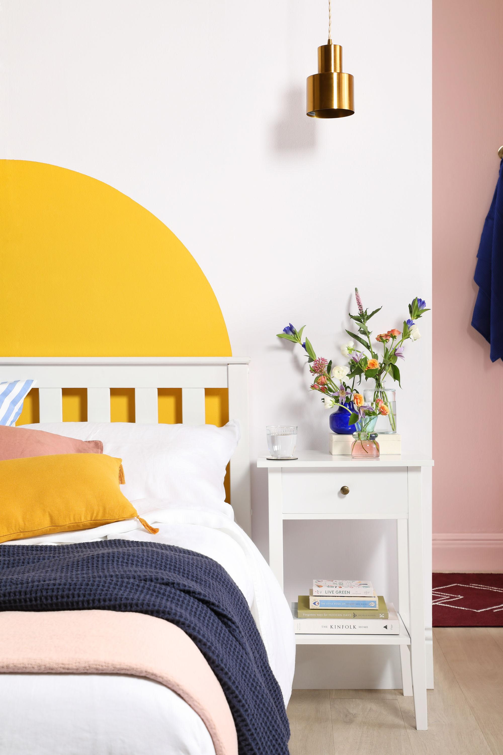 Pink and yellow bedroom with DIY painted headboard, striped, pink and mustard cushions and a white bed