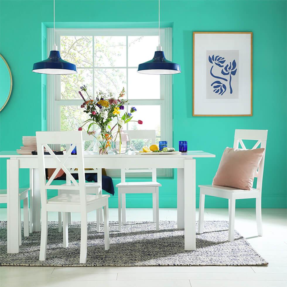 Pastel turquoise dining room with white wooden dining set, blue lamps and glassware, pink cushion and a grey rug