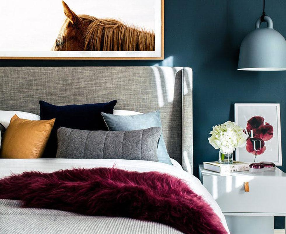 Bedroom with burgundy fur throw, teal wall and ochre pillow.