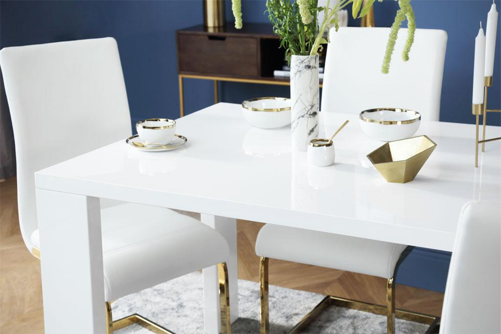 A glossy white dining set with gold decorations and ornaments.