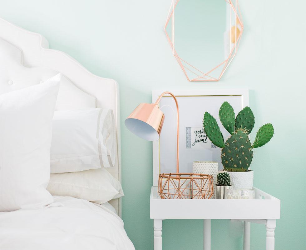 A white bedroom with a pink lamp and a cactus.