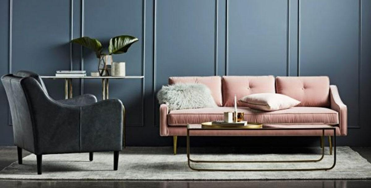 A pale pink sofa set against a dark teal wall.