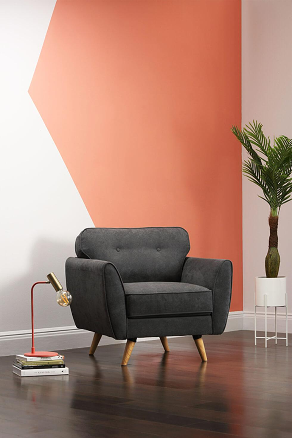 Coral colour blocked wall with grey armchair