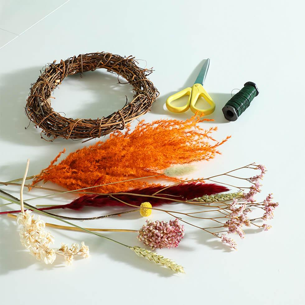 Materials needed to create a spring floral hoop include a rattan hoop, dried flowers and florist wire