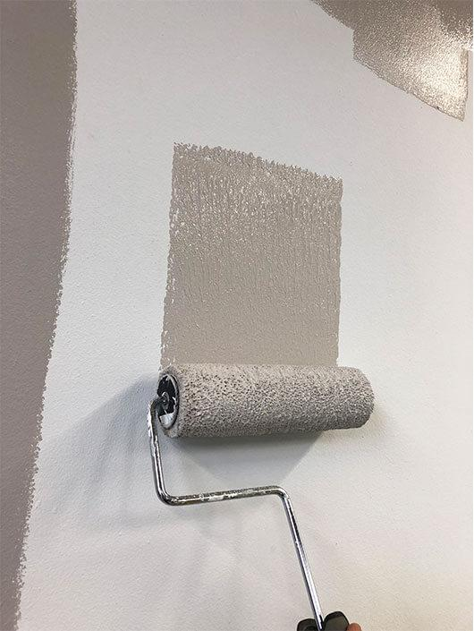 Painting a white wall with grey paint.