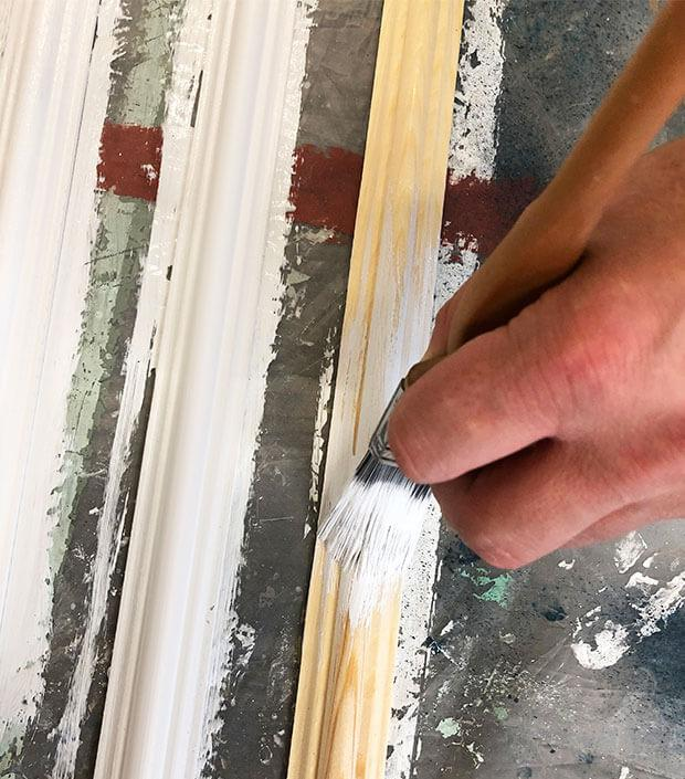 Painting decorative beadings in white.
