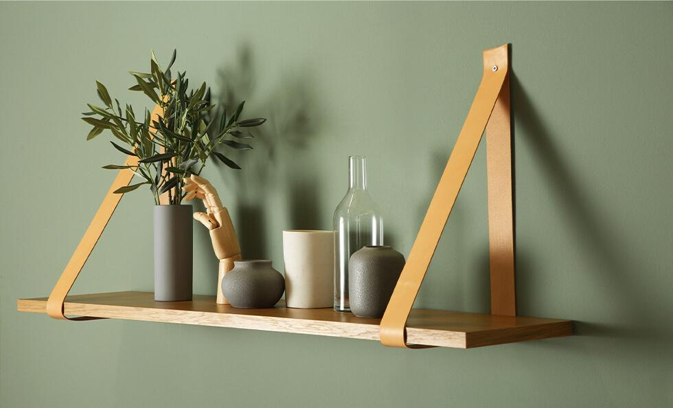Elegant and minimal leather strap shelf with decorative vases and a plant