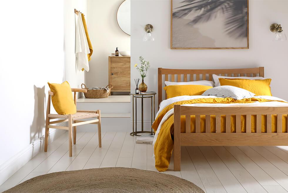 White and yellow bedroom with solid oak bed