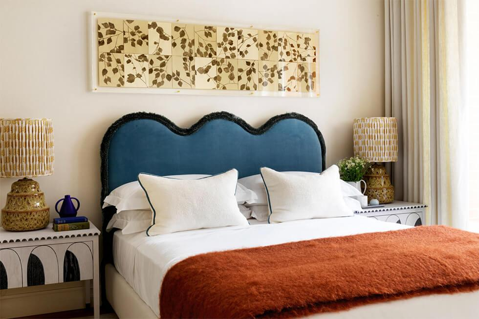 Bedroom with statement headboard, lamp and lacquer art