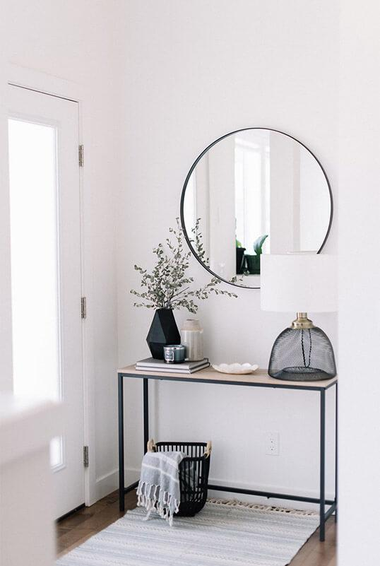 White entryway with black mirror, lamp and vase