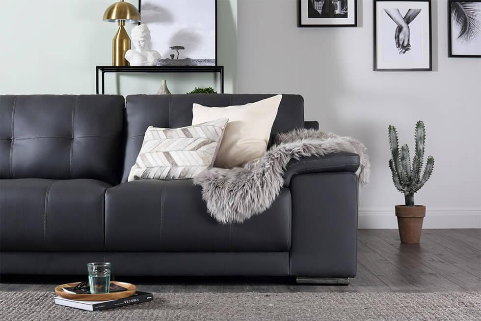 black framed art and grey leather sofa in a modern living room