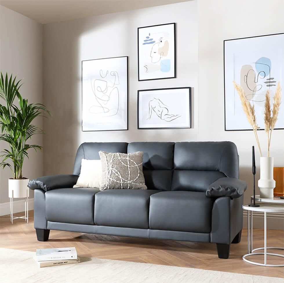Grey leather sofa in a living room with black framed art and accessories