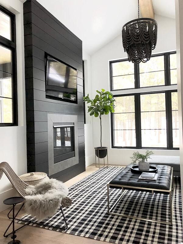 Black living room with fireplace, chandelier and patterned rug