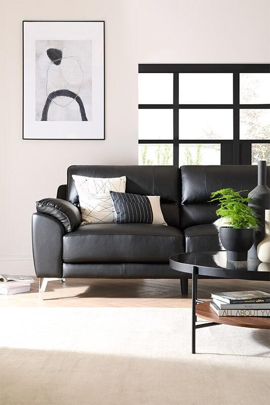 Black leather sofa with chrome legs in an industrial living room