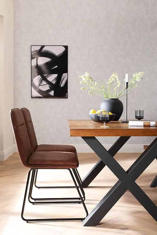 Wooden dining table with black painted legs and brown and black dining chairs