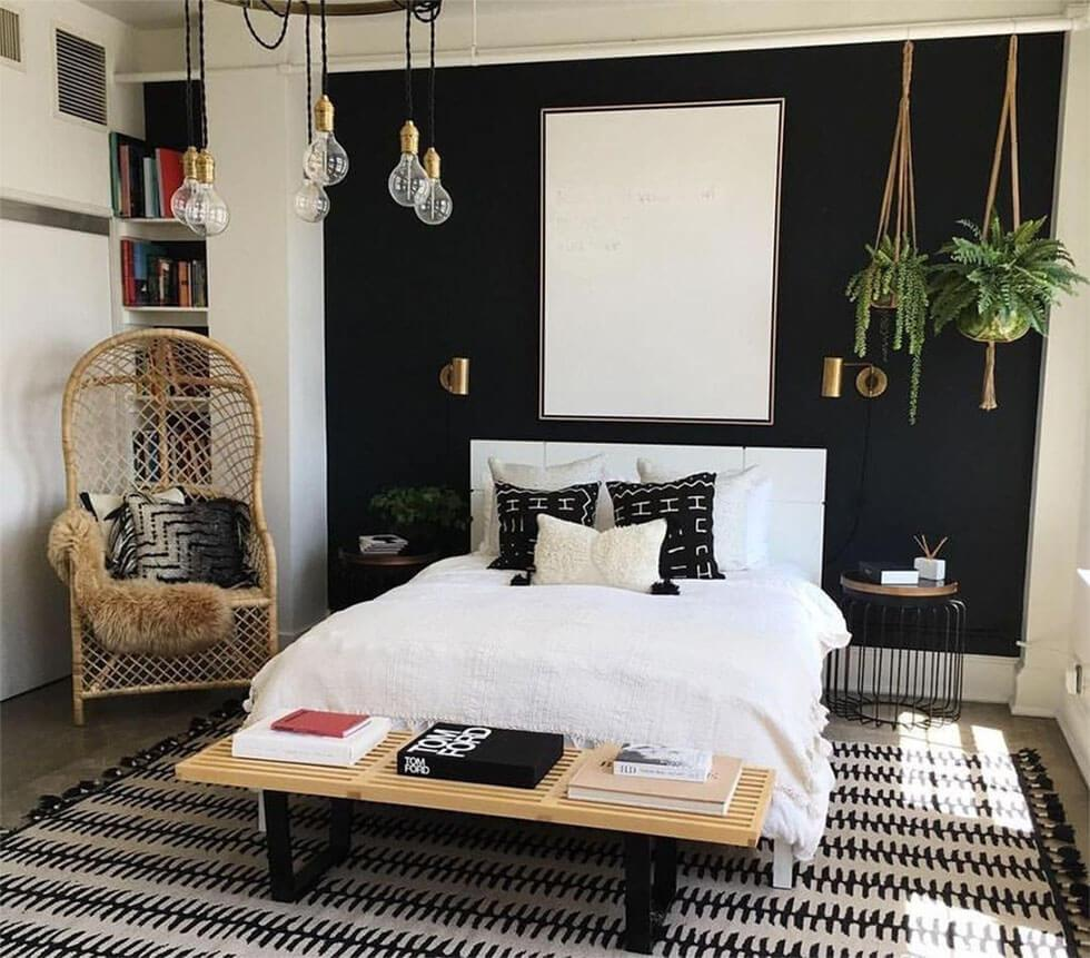 Black and white tropical bedroom with rattan chair, macrame plant hangers and indoor plants