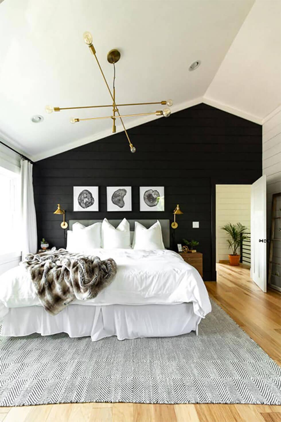 Modern black and white bedroom with rustic touches, a gallery wall, wood floors and a brass chandelier