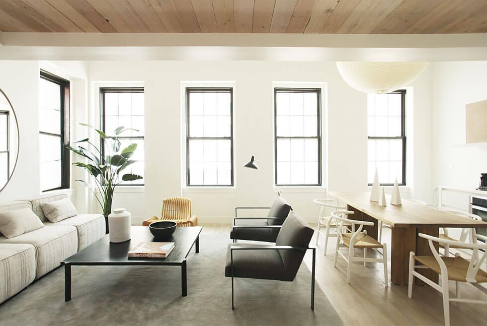 Neutral open plan living area with large windows, light grey sofa, light wood dining set and rattan armchair