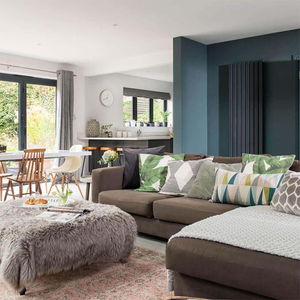 Open plan living space with a grey corner sofa and a dark green feature wall