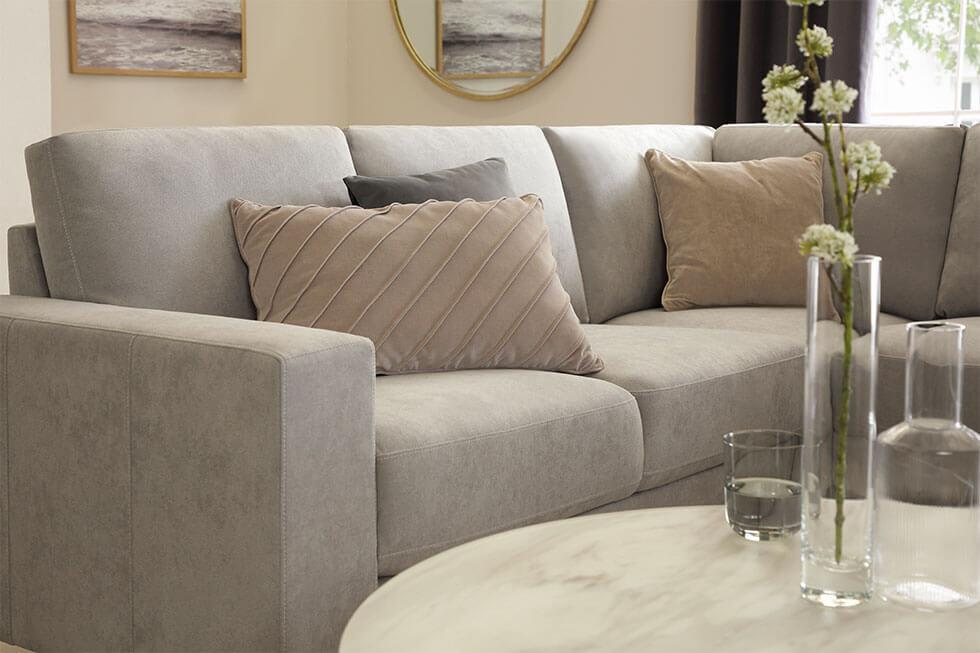 Close up of light grey fabric corner sofa with soft cushions, and a light wood coffee table