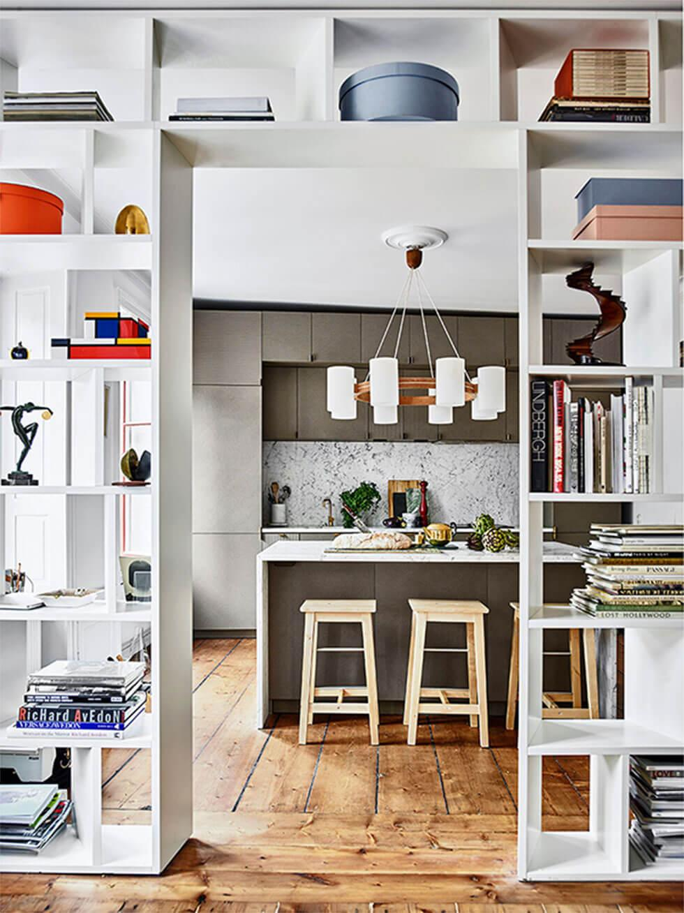 An airy open plan living space with white bookshelves dividing the room
