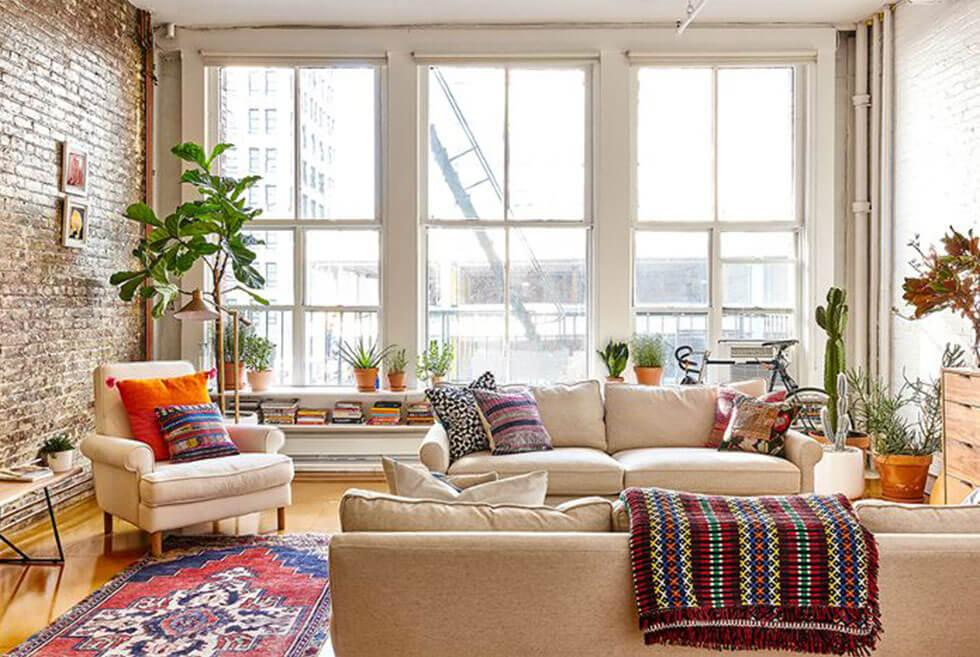 Eclectic, cosy living room with brick feature wall, cream sofa set, colourful rug and a reading nook