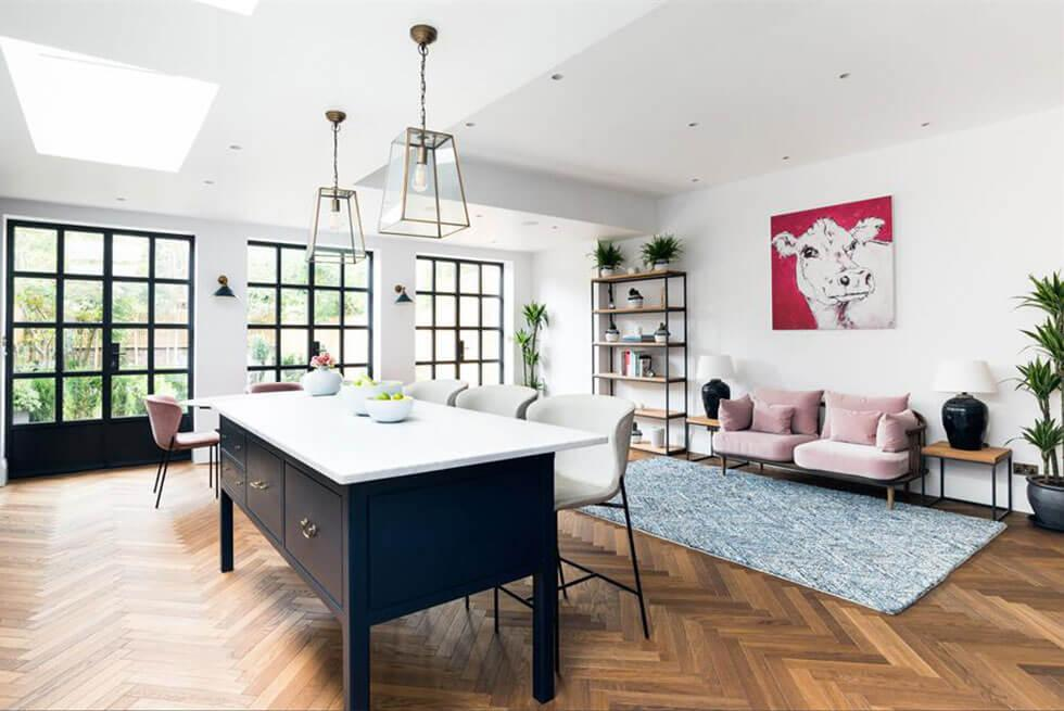 Large open plan living area with a black and white kitchen island, pale pink sofa, cosy rug and bold artwork and lighting