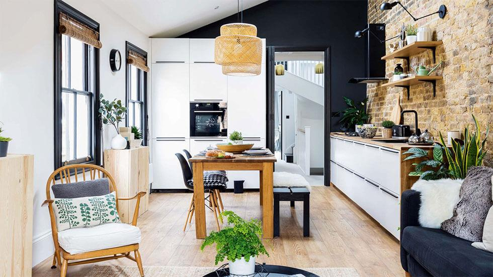 Open plan living and dining area with a wood dining set, an exposed brick feature wall, and a colour palette of black, white and wooden hues.