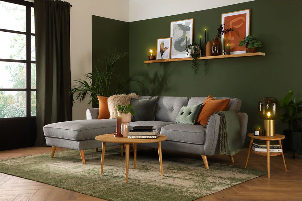 Cosy neutral living room with grey fabric corner sofa, round mirror and cushions