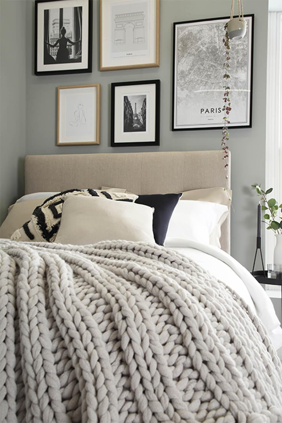 Fabric bed with knitted blanket and framed gallery wall
