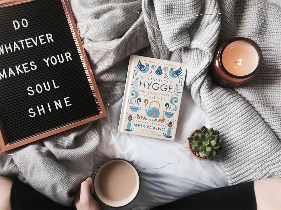 Flat lay of book, a mug and a candle