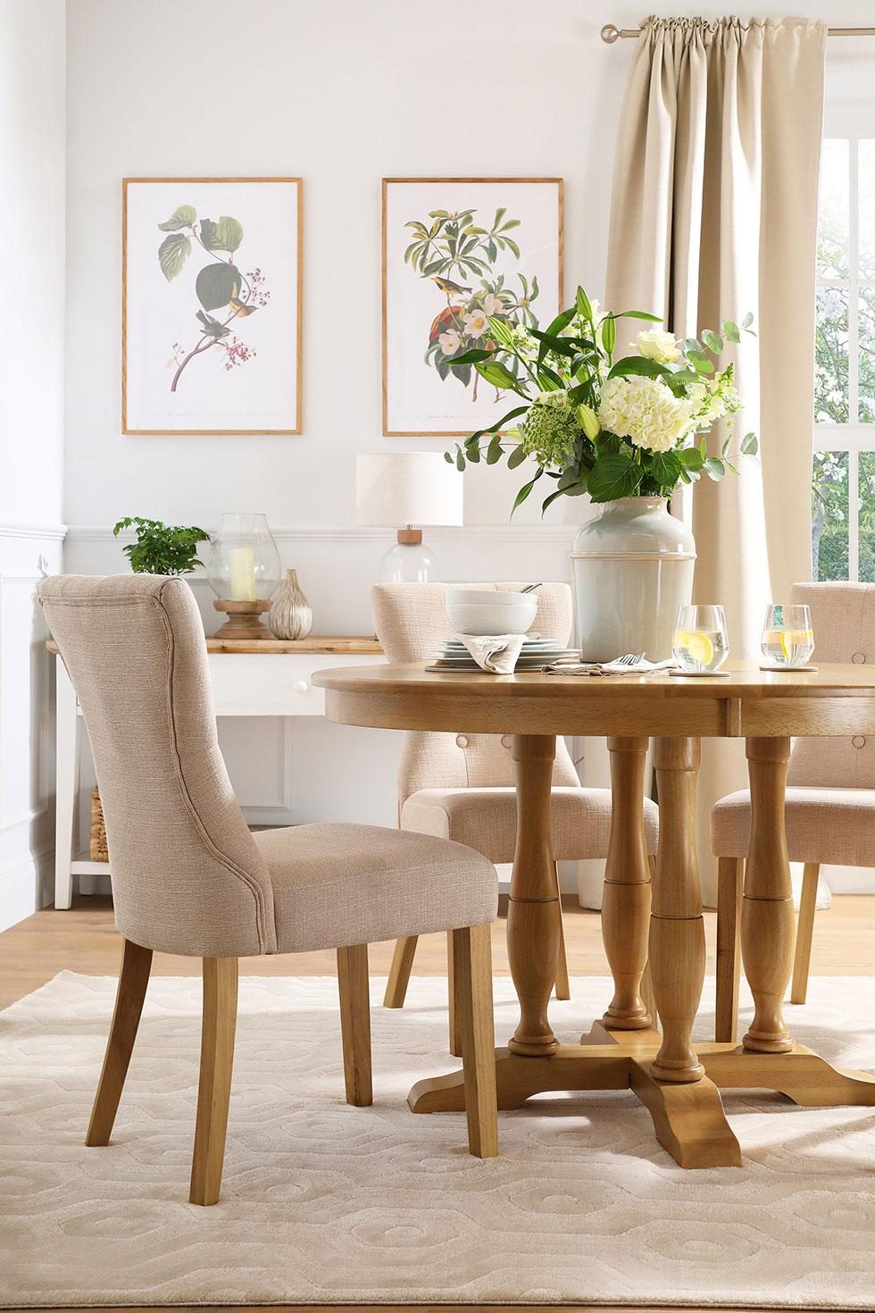 Neutral dining room with round wooden dining table and light fabric chairs