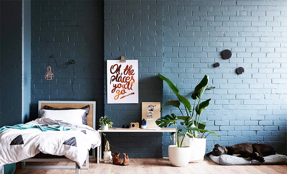 Dark blue bedroom with brick walls and wooden flooring.