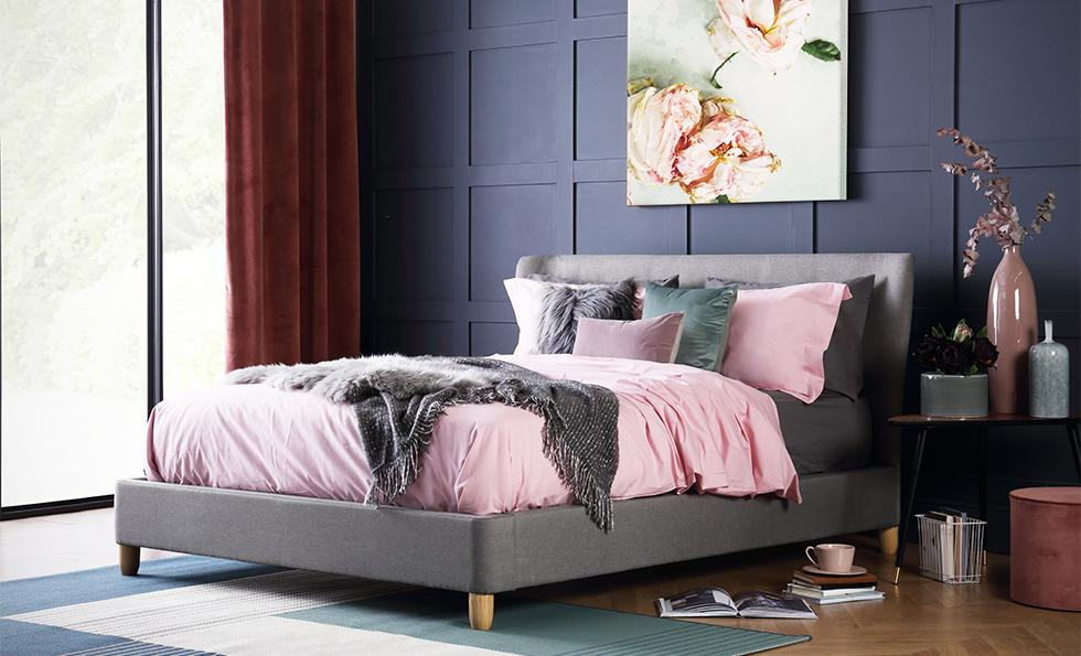 Dark bedroom with grey fabric bed and pastel sheets.