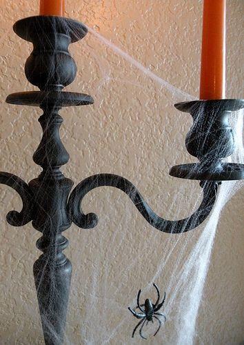 Fake cobwebs and spider on a black candelabra.