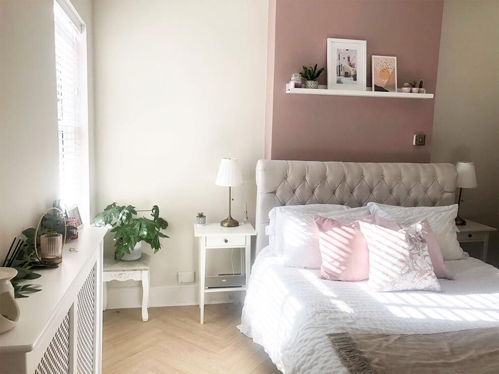 Cosy and elegant bedroom with tufted Chesterfield bedframe and pink feature wall
