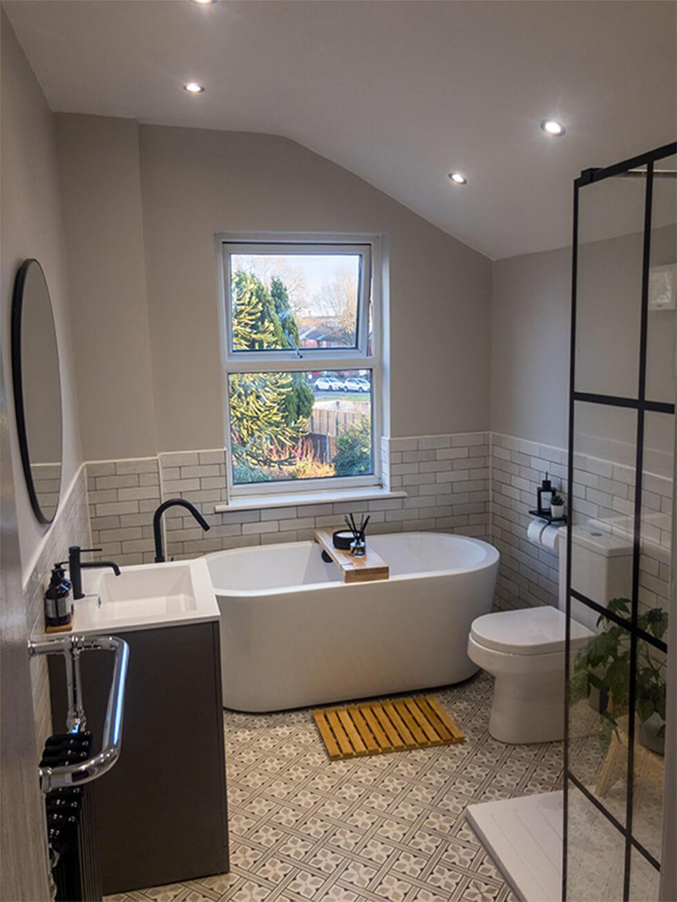 Master bathroom with white bathtub, tiles and black accents