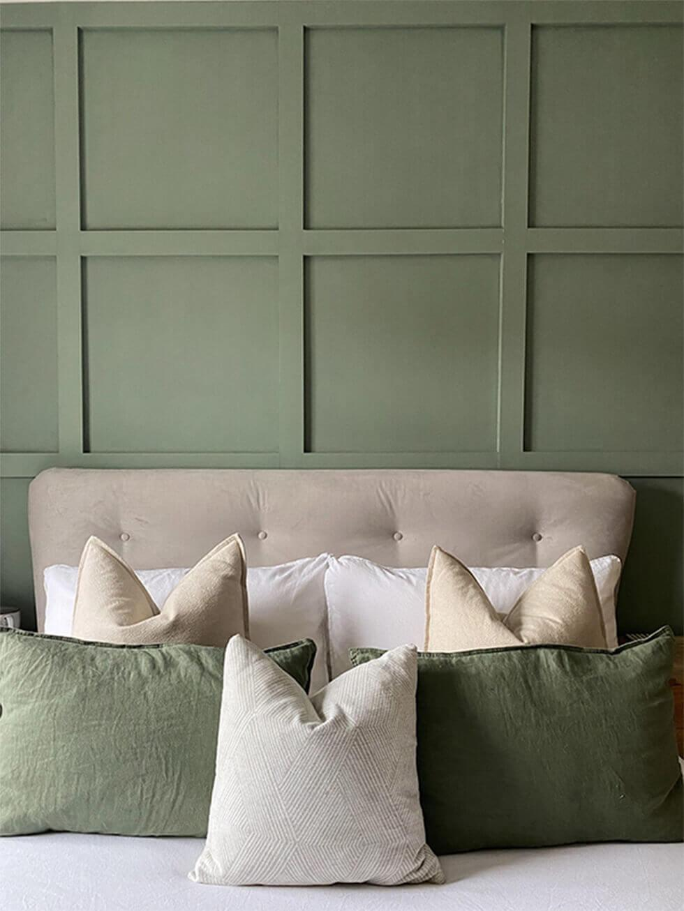 Close up shot of velvet bed headboard, wall panelling and cushions
