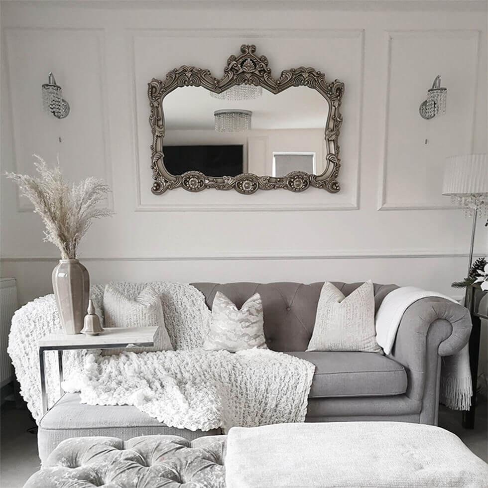Neutral grey and white living room with ornate mirror, grey sofa and pampas grass in a vase