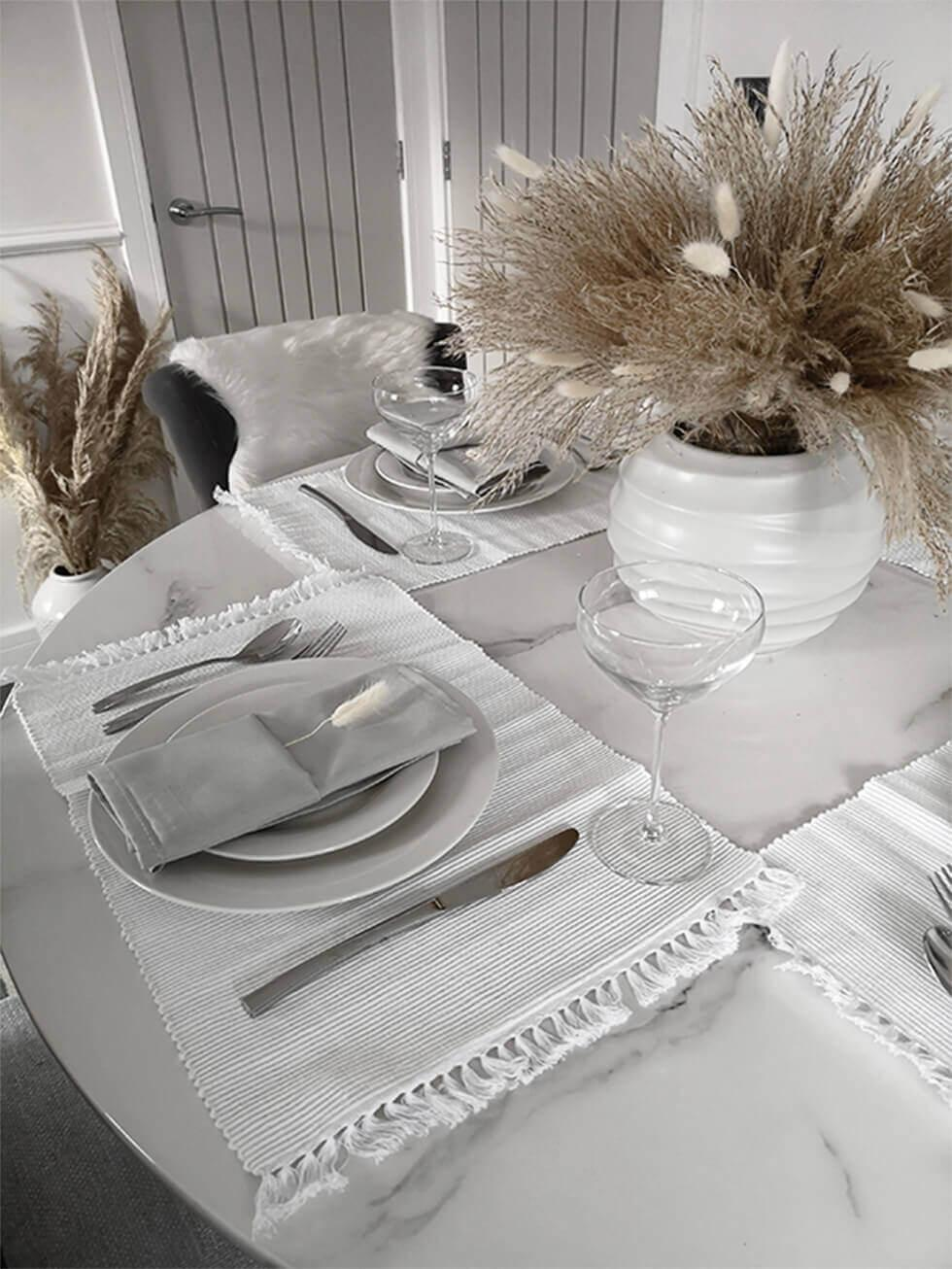 Close up of a dining table setting with a pampas grass centrepiece